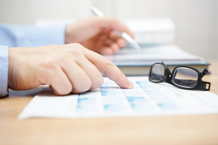 A close of of someone comparing financial documents on a desk, with a pair of reading glasses sitting nearby