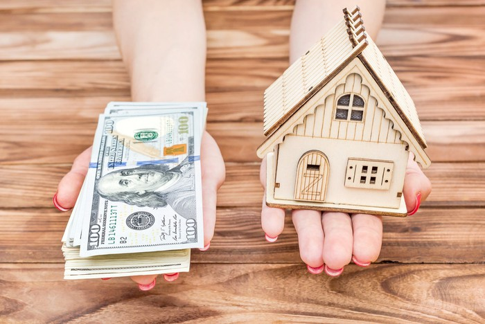 Two hands extended, with cash in one and a small model of a house in the other