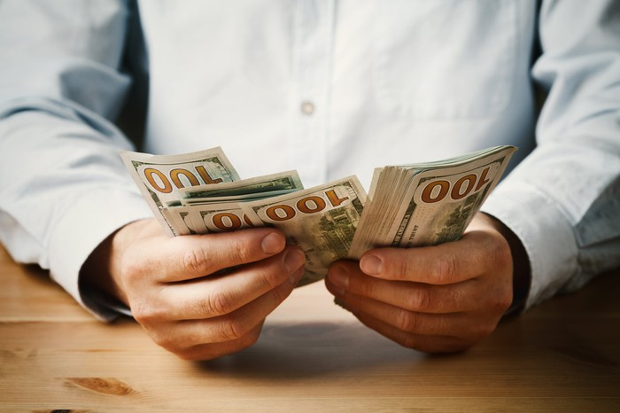 A man counting hundred-dollar bills.