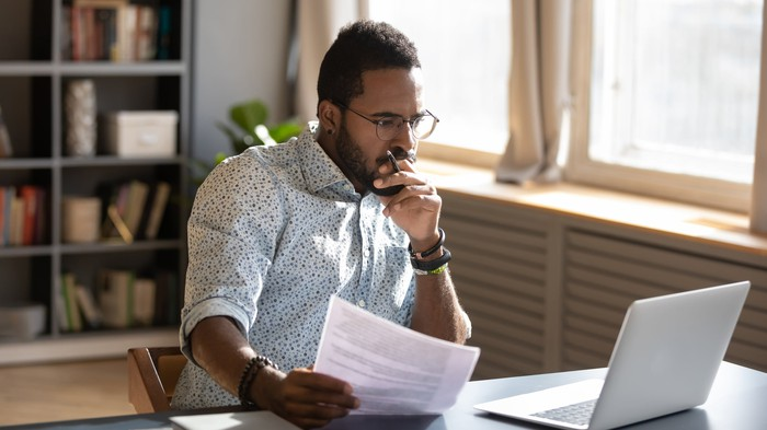 Man at home in front of laptop researching investments for his self-directed IRA.