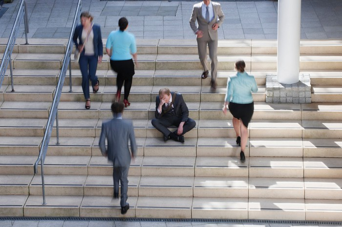 A man sitting on a staircase with people walking past him