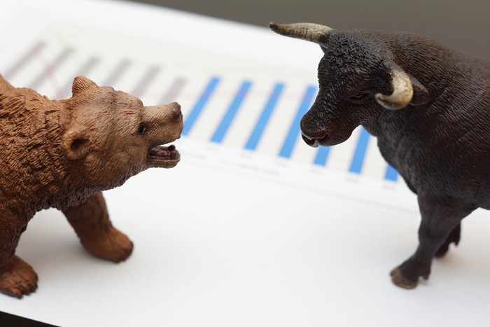 Small bear and bull figurines facing off on top of a piece of paper with a bar graph on it