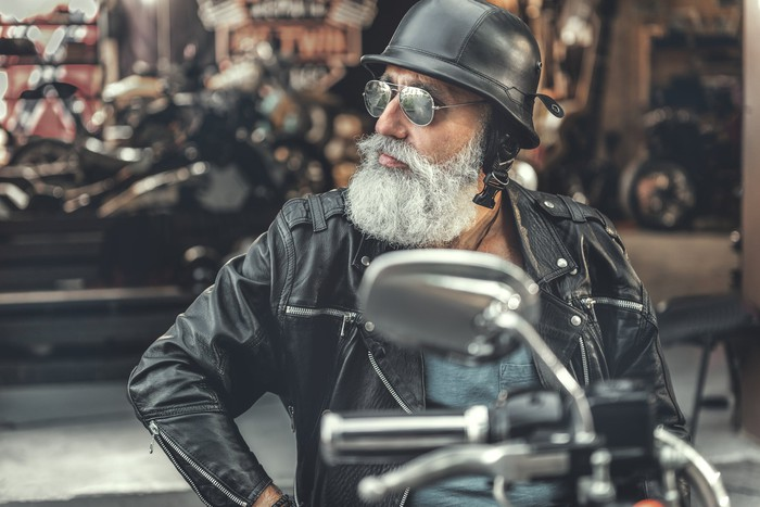 Grey-bearded man wearing sunglasses and helmet astride a motorcycle
