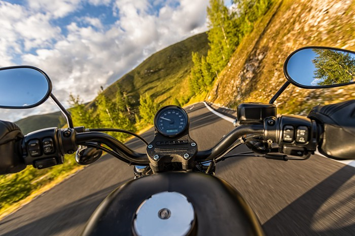 View of autumn countryside over handlebars of a motorcycle