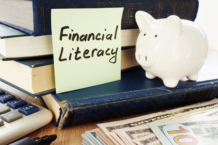 "Stack of books next to a piggy bank, cash, a calculator, and a sticky note that says ""Financial Literacy"""