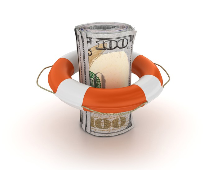 A roll of hundred-dollar bills surrounded by a life preserver.