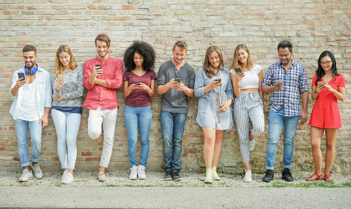 Nine young people leaning against a wall and looking at their smartphones