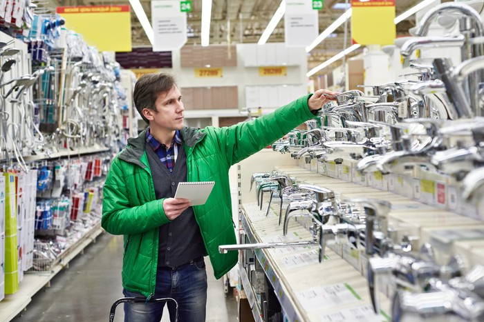 Man examining faucets displayed in home improvement store