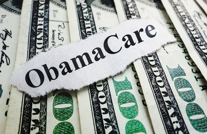 "A strip of paper bearing the words ""ObamaCare"" rests on several hundred-dollar bills."