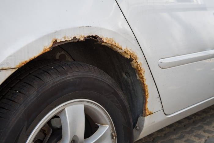 A white car's rusty wheel well.