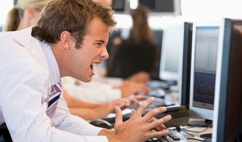 Frustrated Stock Trader in Front of Computer Screen Getty