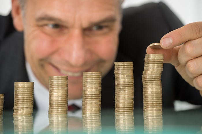 A man happily stacking coins