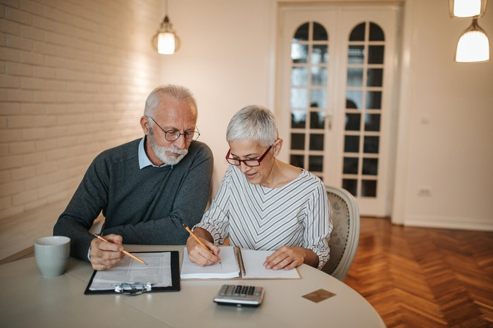 Married couple sitting at a table with papers and a calculator and discussing retirement.