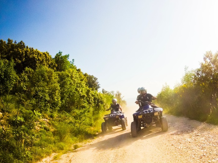 Two people riding ATVs on a dirt road