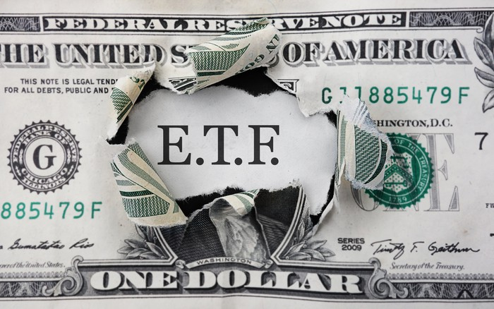 Letters E.T.F. shown through a hole in a dollar bill.