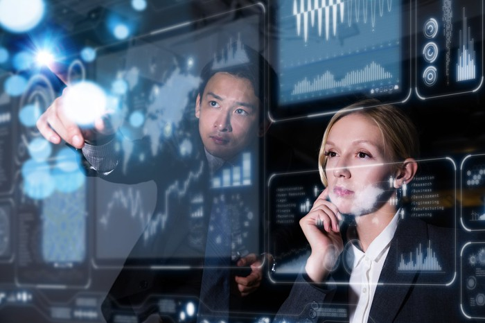 Two people looking at a panel of electronic screens displaying stock information