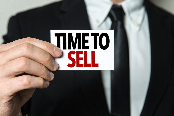 "Man with a suit holding a sign that says ""TIME TO SELL."""