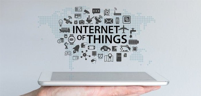 "Image a person holding a tablet with the words ""Internet of Things"" above it and small images of everyday objects above it."