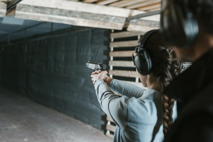 Woman holding handgun at shooting range with instructor behind her