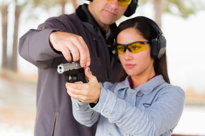 Woman at gun range getting instruction on using a handgun.