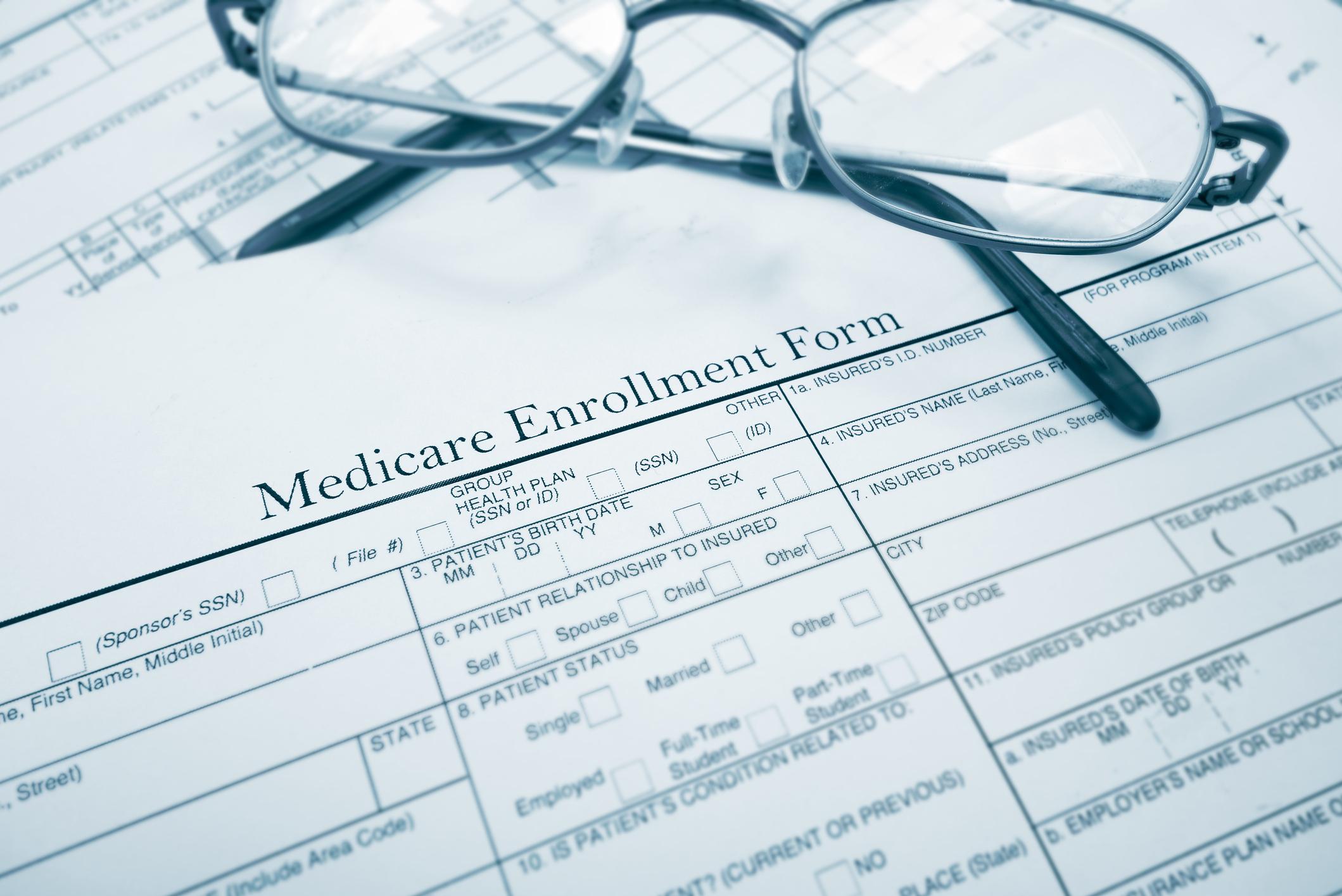 Reading glasses rest atop a Medicare enrollment form.
