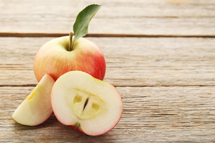A whole apple and a split apple on a wooden table.