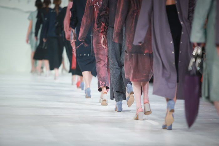 The lower bodies of a parade of fashion models on a runway.