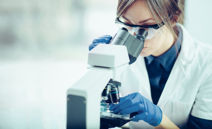 Female scientist in lab coat looking through microscope