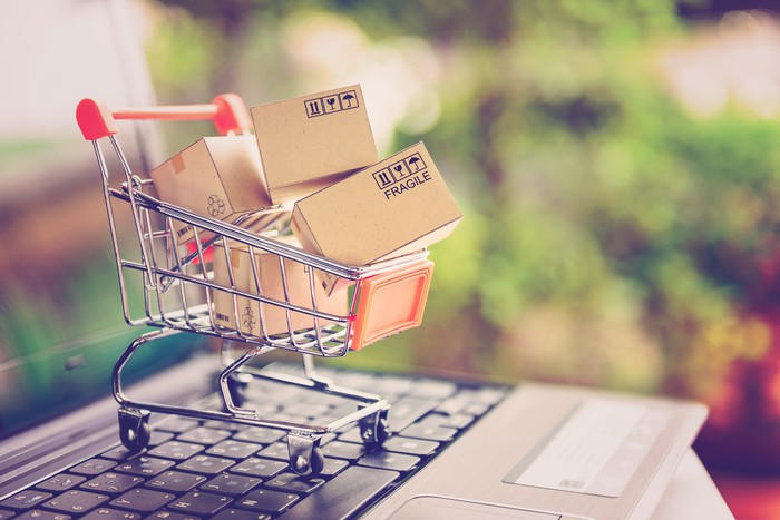 A mini shopping cart filled with tiny cardboard shipping boxes sits on a laptop keyboard.