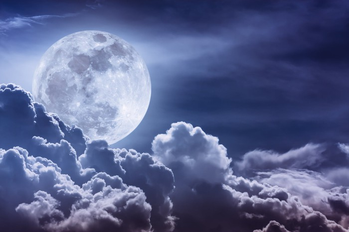 Moon in night sky with white fluffy clouds beneath it