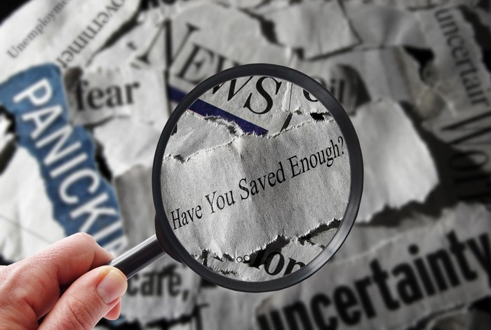 "A magnifying glass over the words ""Have You Saved Enough"" on top of newspaper headlines."