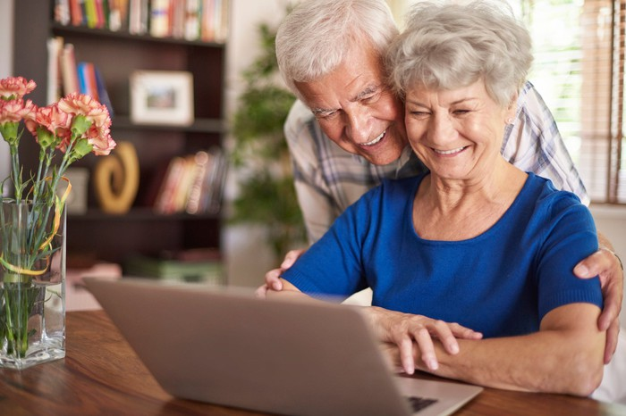 Older man and woman looking at laptop