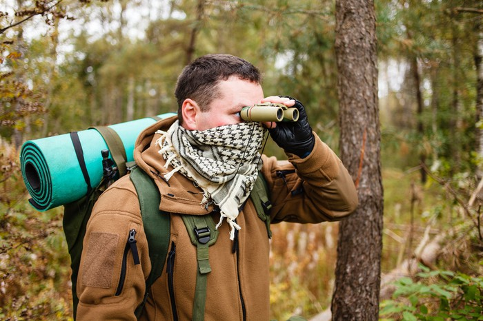 A man wearing a backpack and a bandana peers through binoculars in the woods