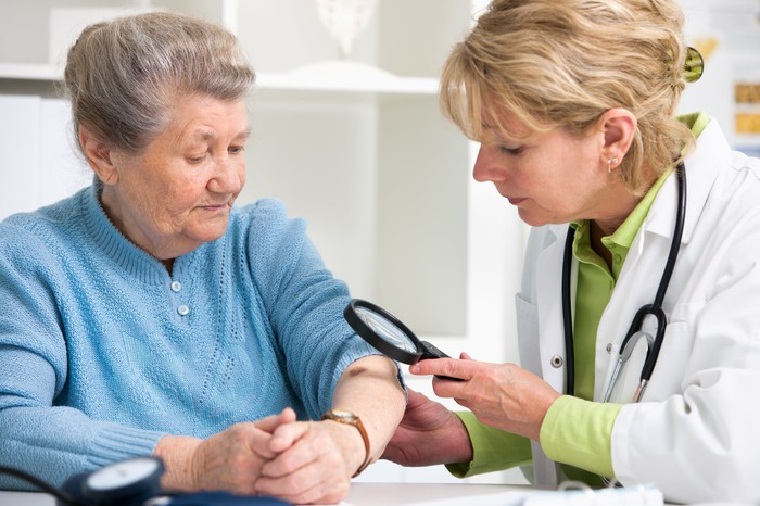 A female doctor uses a magnifying glass to examine an older female patient's arm