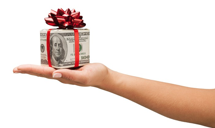 An outstretched arm and hand holding a box made of $100 bills with a bow on top.
