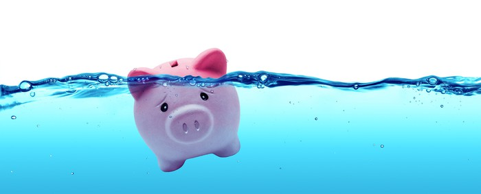 A piggybank floating in blue water.