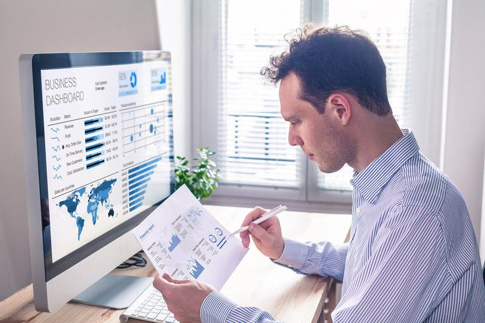 An investment banker checking charts on paper and computer screen.