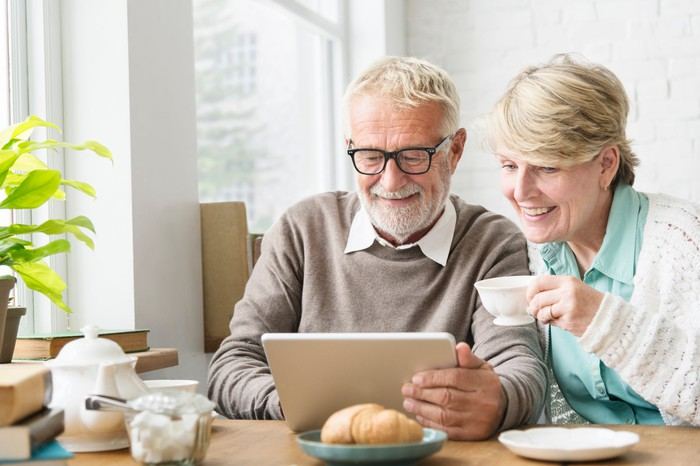 An older couple sitting at a table using a tablet and drinking coffee.