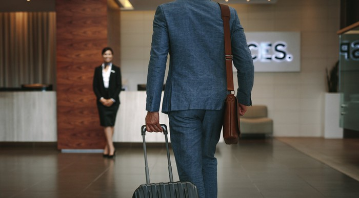 Man in suit wheeling his bag up to a hotel check-in desk where a female employee waits