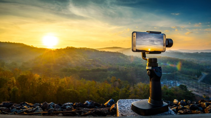 A GoPro camera in the foreground; a sunset/sunrise in the background