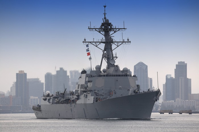 USS Stockdale at sea with a city skyline in the background