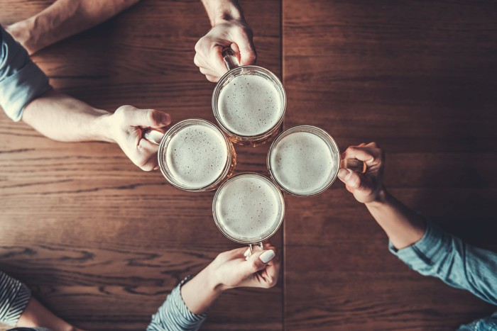 Overhead view of four people's arms toasting with beer steins
