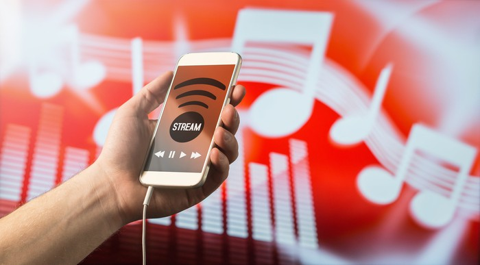 A mobile phone displays a music streaming app against an abstract background of digital music.