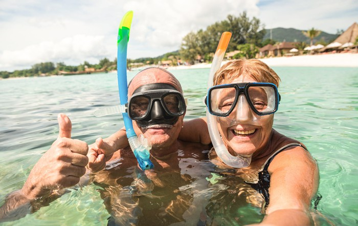 An elderly couple smiles while snorkeling in the ocean.