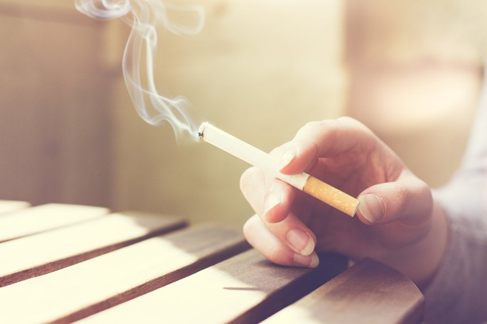 A hand holding a lit cigarette