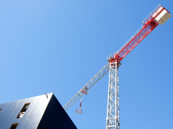 A red and white crane hovers over a gray building.