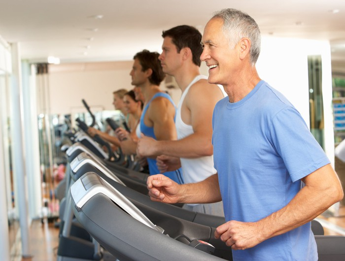 Men and women lined up exercising on treadmills.