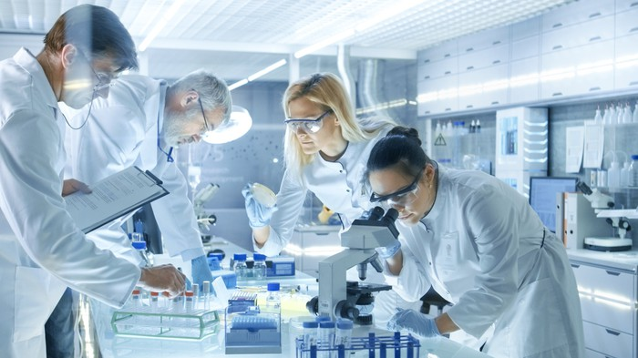 Four professionals in white coats working in a lab.