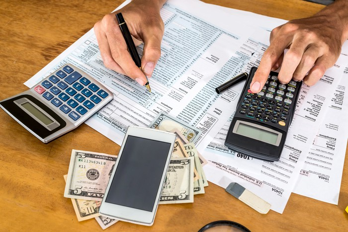 On a desk: Calculators, cash, a smartphone, and two hands writing on tax forms