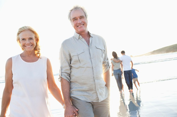 Male and female couple in their 60s walking on the beach.